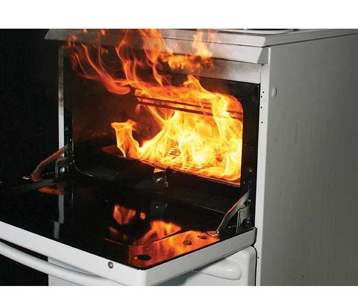 An open oven with flames pouring out